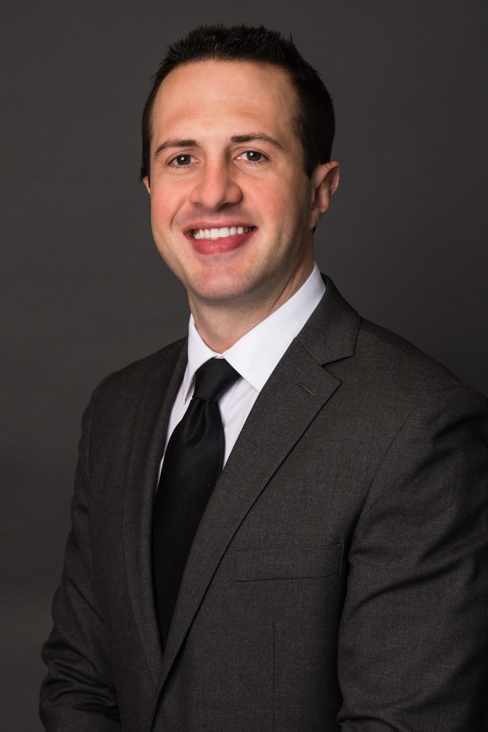 a man wearing a suit and tie smiling at the camera